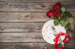 Arrangement romantique de table avec un plat blanc et des roses rouges Photos libres de droits