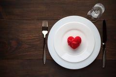 Arrangement romantique de table pour le jour de valentines avec le coeur rouge d'un plat Photo stock