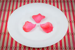 Arrangement of rose petals on a plate. Stock Photos