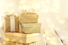 Beautiful golden presents for Christmas. Arrangement of shiny bright boxes decorated with ribbons in glowing lights stock photography