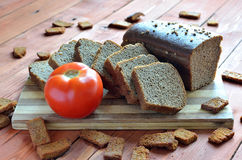 Arrangement of slices of black bread and a tomato on a wooden ta Royalty Free Stock Image
