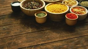 Arrangement of spices in small bowls. Collection of various spices and condiments in small bowls arranged on shabby wooden table stock video footage