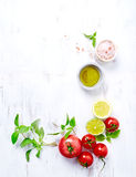 An arrangement of tomatoes, basil, olive oil and himalayan salt Royalty Free Stock Images