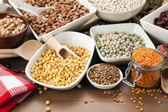 Arrangement of various legumes in bowls on table. Variety of legumes in bowls and glasses, arranged on kitchen table Royalty Free Stock Images