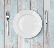 Arrangement vide blanc de plat de dîner sur la table en bois bleue images stock