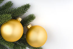 Arrangement of Winter Holyday decoration. Christmas decoration: closeup on two golden balls and spruce branch. Space for your text or announcement Stock Images