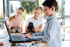 Arrangements changeants de beau garçon d'un robot sur l'ordinateur portable Photographie stock libre de droits