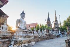 Arrangera i rak linje sittande Buddhastatyer med forntida fördärvar av templet på waen Arkivbilder