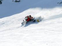 Arrangera i rak linje snowcat skidar pisten arkivbild