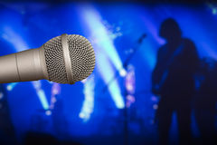 Arrangera mikrofonen med en gitarrist på den tillbaka oskarpa bakgrunden arkivfoton