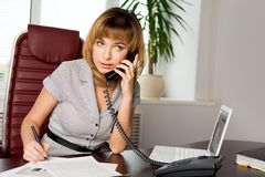 Arranging an appointment. Portrait of serious businesswoman listening to her partner on the phone in office Stock Photos