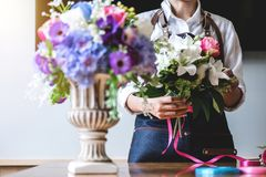 Arranging artificial flowers vest decoration at home, Young woman florist work making organizing diy artificial flower, craft and. Hand made concept stock image