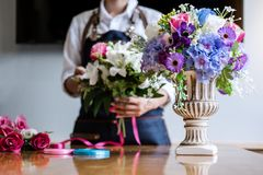 Arranging artificial flowers vest decoration at home, Young woman florist work making organizing diy artificial flower, craft and royalty free stock photo