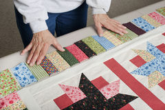 Arranging fabric for piano key border. A quilter arranges fabric to assemble a piano key border to finish a quilt top Royalty Free Stock Photo