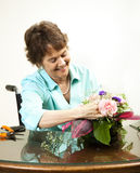 Arranging Flowers. Pretty disabled woman arranging a bouquet of flowers stock photo