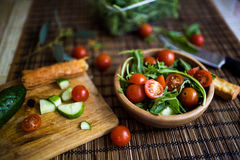 Arranging fresh green salad with cucumbers and tomatoes Royalty Free Stock Photo
