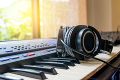Arranging a new song . Headphone and electric piano ready for a song writer Royalty Free Stock Photography