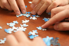 Arranging puzzle pieces Stock Photography