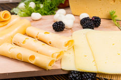 Arranging slices of assorted cheeses on a board Royalty Free Stock Photos