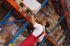 Arranging Stocks. A worker in a factory keeping packages of finished products on the shelves in a storeroom royalty free stock photography