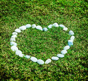 Arranging white stone on the green grass in heart concept Royalty Free Stock Photo
