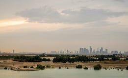 Arranha-céus da cidade de Abu Dhabi da distância coberta com as nuvens imagem de stock royalty free