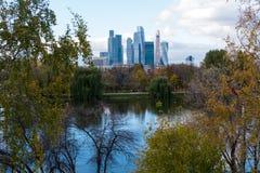 Arranha-céus da cidade de Moscou através das árvores e da lagoa Fotos de Stock Royalty Free