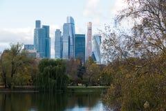 Arranha-céus da cidade de Moscou através das árvores e da lagoa Fotografia de Stock Royalty Free