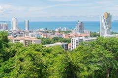 Arranha-céus da construção coberto com as árvores e o mar próximo com SK azul Imagens de Stock
