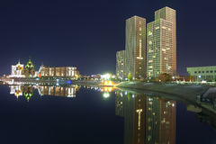 Arranha-céus e reflexão no rio nocturno Fotografia de Stock
