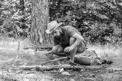 Arranje os galhos das madeiras ou as varas de madeira que est?o como uma pir?mide e coloque as folhas abaixo Guia final ?s foguei fotos de stock