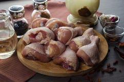 Arranjo cru fresco dos pés de galinha na placa de corte da cozinha Imagens de Stock