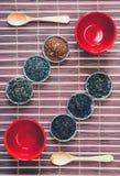 Arranjo das folhas de chá de variedades diferentes de copos vermelhos e de colheres de madeira na esteira de bambu Fotos de Stock Royalty Free