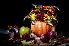 Arranjo de flor em uma abóbora Ainda vida com uma abóbora, as flores e as maçãs Fundo escuro Imagens de Stock Royalty Free