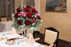 Arranjo do casamento com rosas vermelhas, orquídeas e eucalipto na tabela de banquete fotografia de stock