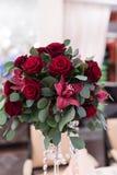 Arranjo do casamento com rosas vermelhas, orquídeas e eucalipto na tabela de banquete imagens de stock