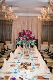 Arranjo do casamento com rosas vermelhas, orquídeas e eucalipto na tabela de banquete foto de stock royalty free