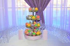 Arranjo do casamento com um carrinho colorido dos queques Imagem de Stock