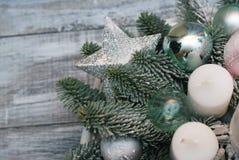 Arranjo do Natal com galhos do pinho, cones e a estrela de prata no fundo de madeira cinzento imagem de stock