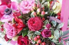 Arranjo floral bonito de flores vermelhas, do rosa e da Borgonha em uma caixa de madeira cor-de-rosa imagens de stock royalty free