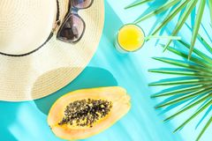 Arranjo liso da configuração de Straw Hat Sunglasses Tall Glass com fruto tropical Juice Papaya Palm Leaf do citrino fresco no fu imagem de stock