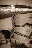 Arranque os cargos ligados em uma corrente em um cais Fotografia de Stock Royalty Free