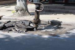 Arrastado ao trator com um jackhammer rasgou fora a seção danificada do asfalto para a restauração fotografia de stock royalty free