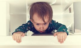 Arrastre caucásico lindo del bebé a través del espacio apretado bajo la mesa de centro hacia cámara imagenes de archivo