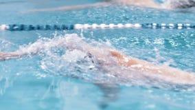 Arrastre de la natación del hombre de la vista lateral del alto ángulo en la cámara lenta del waterpool almacen de video