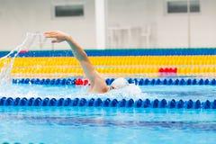 Arrastre de la natación del nadador del hombre en agua azul Imagen de archivo