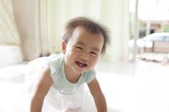 Arrastre del bebé de 10 meses con la cara divertida en la sala de estar casera imágenes de archivo libres de regalías