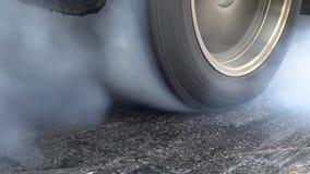 Arrastre el neumático de la quemadura del coche de competición en la línea del comienzo almacen de video