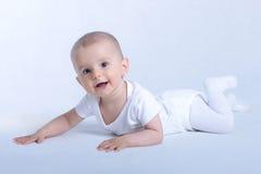 Arrastre feliz del bebé aislado en blanco Fotos de archivo