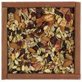 Arrastre la mezcla con las tuercas en un rectángulo de madera Foto de archivo